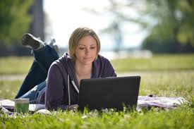 woman laying in grass with laptop